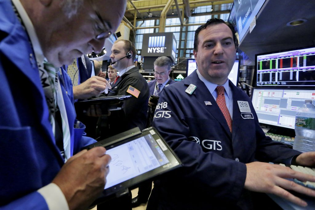 Specialist James Sciulli, right, works with traders on the floor of the New York Stock Exchange on Monday.  (AP Photo/Richard Drew)