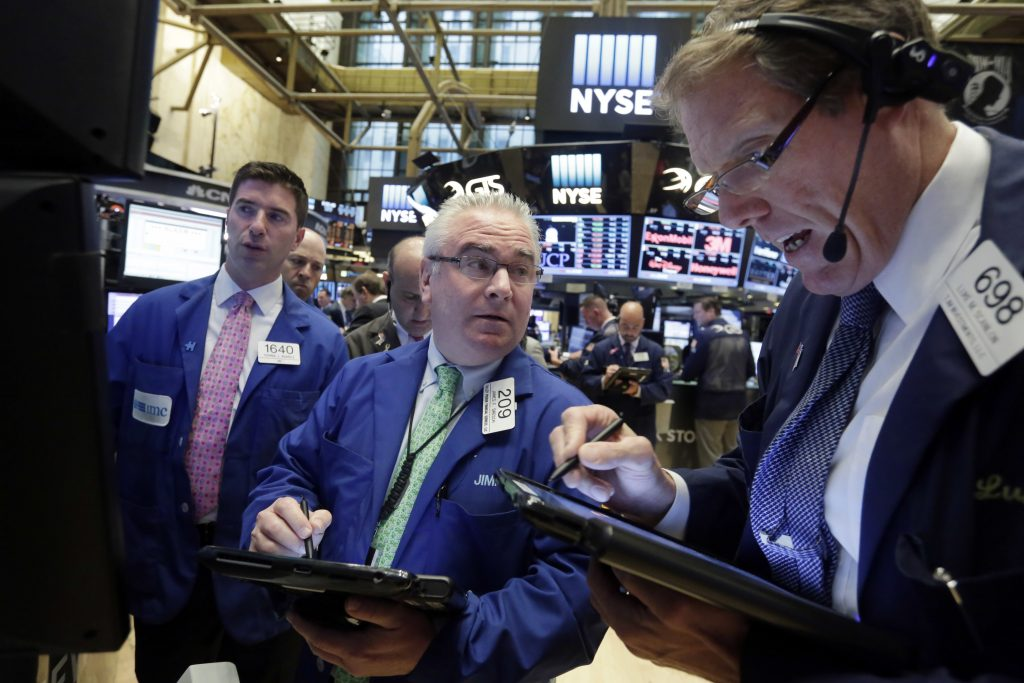 Traders James Dresch, center, and Luke Scanlon, right, work on the floor of the New York Stock Exchange, on Thursday. (AP Photo/Richard Drew)