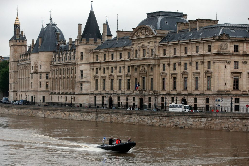 A police boat patrols on the flooding Seine river, in front of the Conciergerie building, a former prison now used partly as a law court, in Paris on Friday. (AP Photo/Thibault Camus)