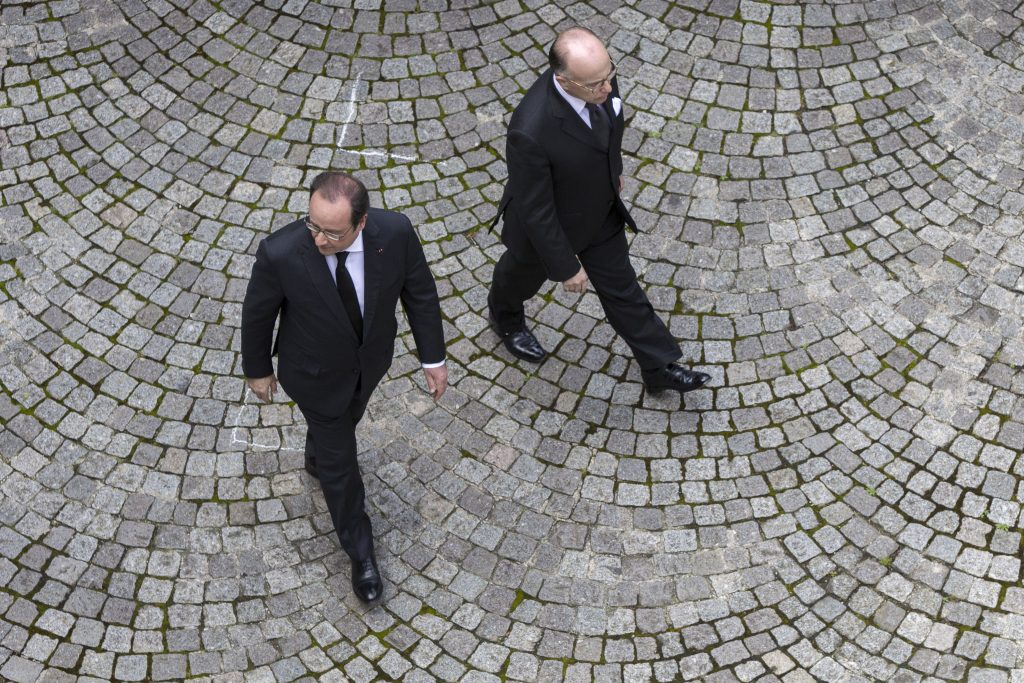 French President Francois Hollande, left, and Interior Minister Bernard Cazeneuve arrive for an homage ceremony for the two police officials killed by an Islamic State extremist, at the French Interior Ministry in Paris, Wednesday, June 15, 2016. The attack revived French concerns about the IS threat after the group targeted Paris last year. (AP Photo/Kamil Zihnioglu)