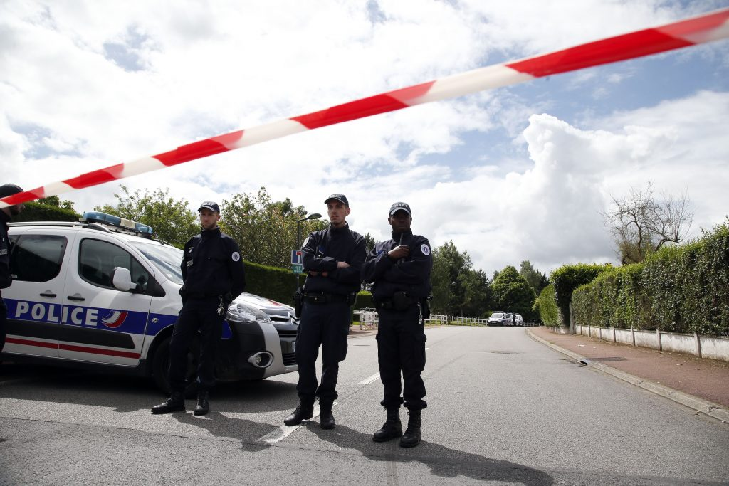 "French police officers block the road leading to a crime scene the day after a knife-wielding attacker stabbed to death a senior police officer and his female companion Monday evening in Magnanville, west of Paris, France, Tuesday, June 14, 2016. French President Francois Hollande says that the stabbing attack that left two police officials dead was ""incontestably a terrorist act."" (AP Photo/Thibault Camus)"