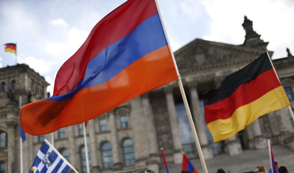 """Supporters wave Armenian and German flags in front of the Reichstag, the seat of the lower house of parliament Bundestag in Berlin, Germany, June 2, 2016, as they protest in favour of approval of a symbolic resolution by Germany's parliament that declares the 1915 massacre of Armenians by Ottoman forces a """"genocide"""". REUTERS/Hannibal Hanschke"""