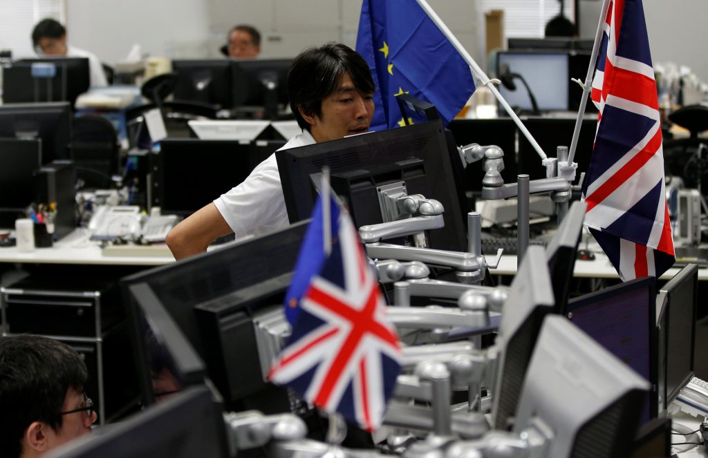 Employees of a foreign exchange trading company work among flags of Britain and EU in Tokyo, Japan, June 27, 2016. REUTERS/Toru Hanai