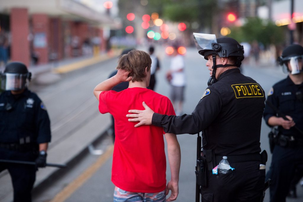 A police officer leads a man to safety after he was chased by protesters against Republican presidential candidate Donald Trump on Thursday, June 2, 2016, in San Jose, Calif. A group of protesters attacked Trump supporters who were leaving the presidential candidate's rally in San Jose on Thursday night. A dozen or more people were punched, at least one person was pelted with an egg and Trump hats grabbed from supporters were set on fire on the ground. (AP Photo/Noah Berger)