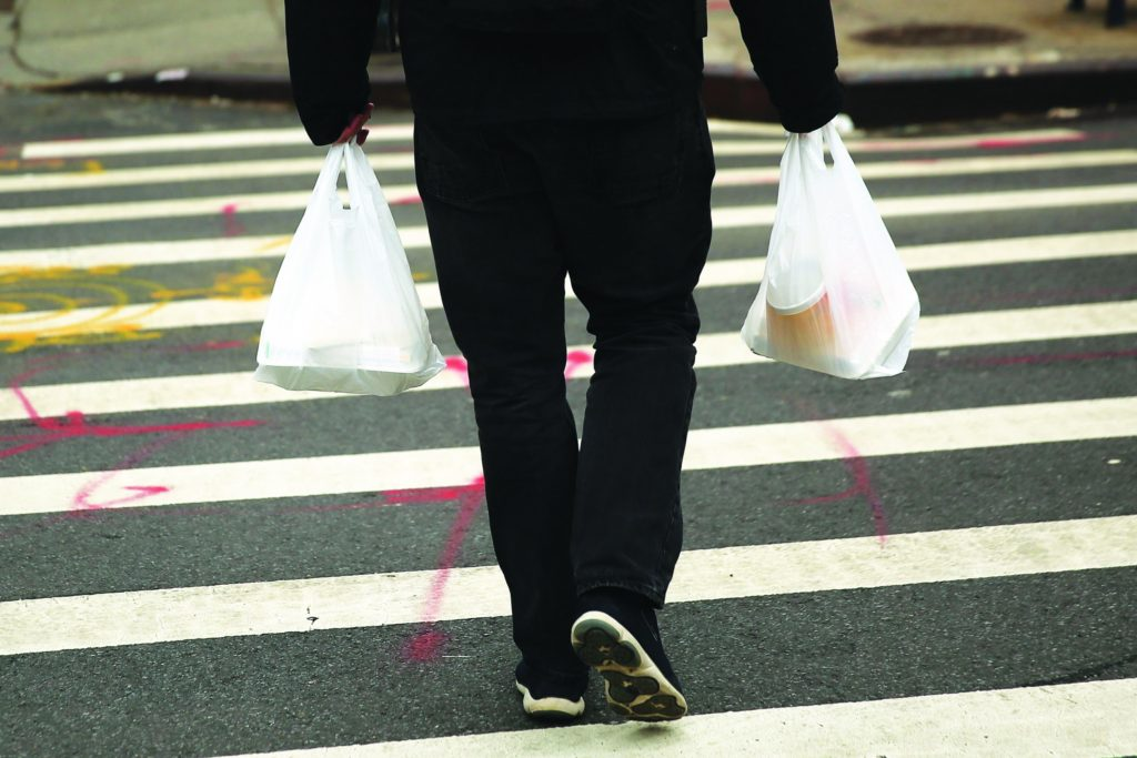 A man walks out of a store in New York City with plastic bags. (Photo by Spencer Platt/Getty Images)