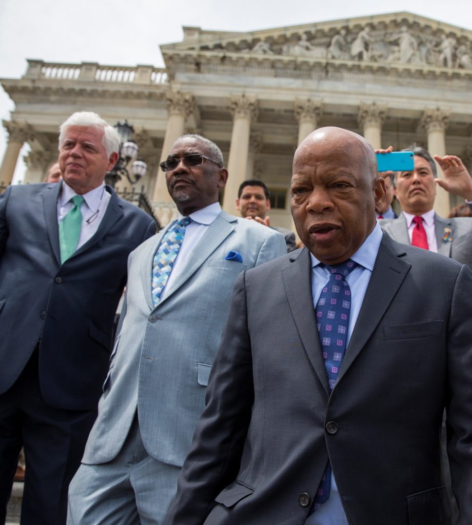Rep. John Lewis, D-Ga., (front right) leads lawmakers down the steps of the Capitol on Thursday, to greet a crowd assembled after House Democrats ended their sit-in protest. (AP Photo/Evan Vucci)