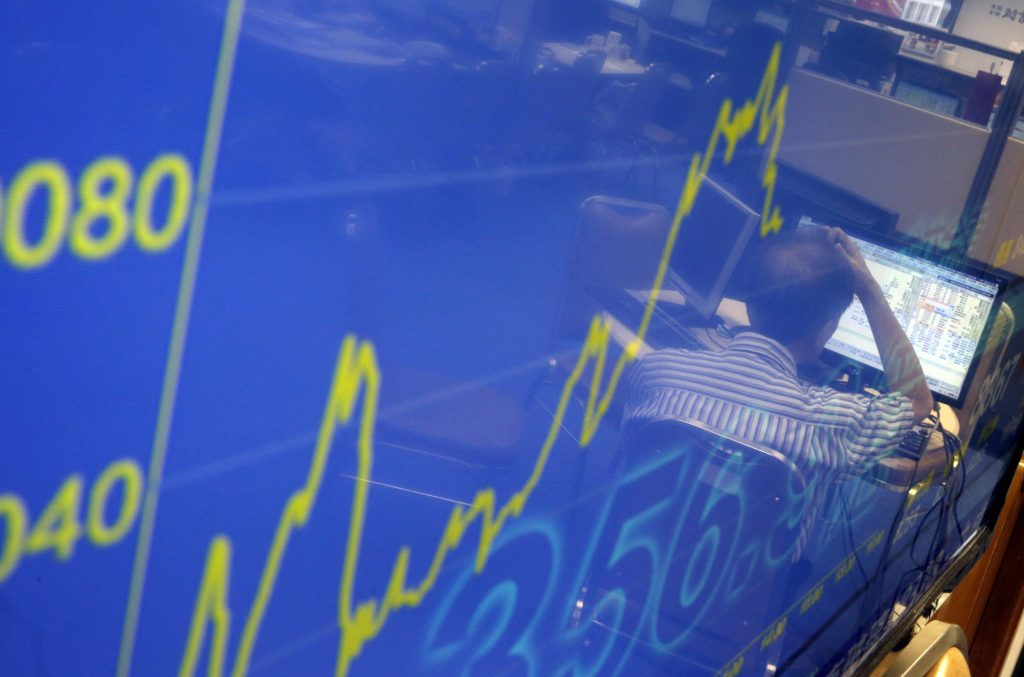A screen shows the Hang Seng Index with the reflection of a broker watching the stock price at a brokerage firm in Hong Kong, Tuesday, June 28, 2016. Most Asian stock benchmarks slipped on Tuesday as Britain's vote to quit the European Union and its messy aftermath continued to reverberate throughout global financial markets. (AP Photo/Kin Cheung)