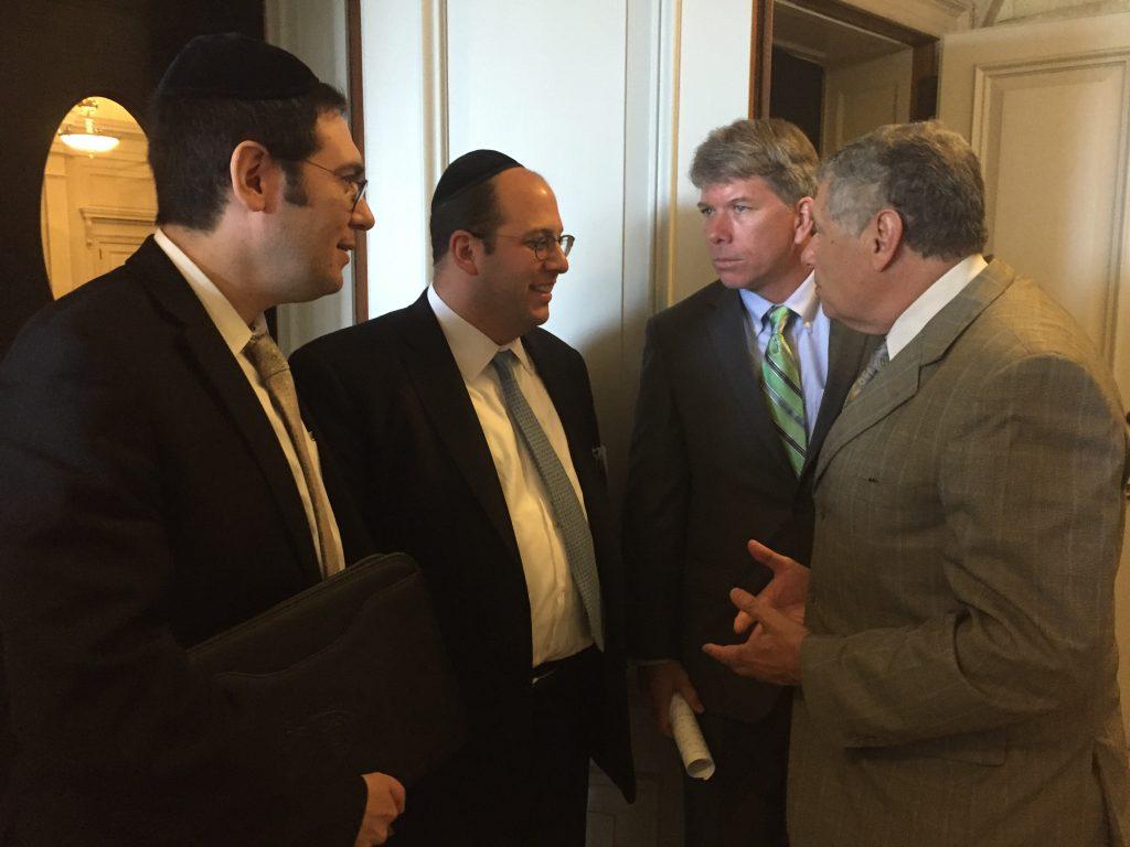 (L-R) Lakewood Mayor Menashe Miller, Rabbi Avi Schnall of Agudath Israel, Assemblyman Sean Kean and Senator Bob Singer discussing the busing bill in Trenton this week.