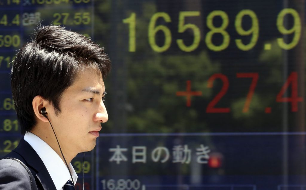 A man walks by an electronic stock board of a securities firm in Tokyo, Friday, June 3, 2016. Asian shares were mixed Friday as investors awaited a U.S. jobs report later in the day and action from the U.S. Federal Reserve later in the month. (AP Photo/Koji Sasahara)
