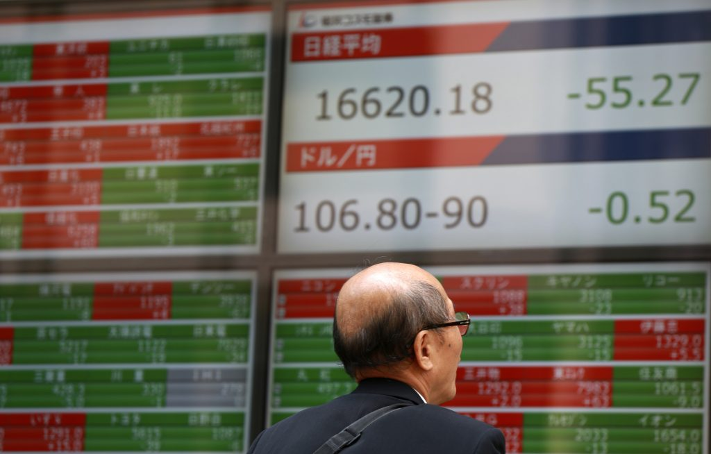 A man watches an electronic stock board showing Japan's Nikkei 225 index at a securities firm in Tokyo Wednesday, June 8, 2016. Asian stocks were mostly lower Wednesday after the World Bank cut its global growth forecast and investors looked ahead to Chinese trade data. (AP Photo/Eugene Hoshiko)
