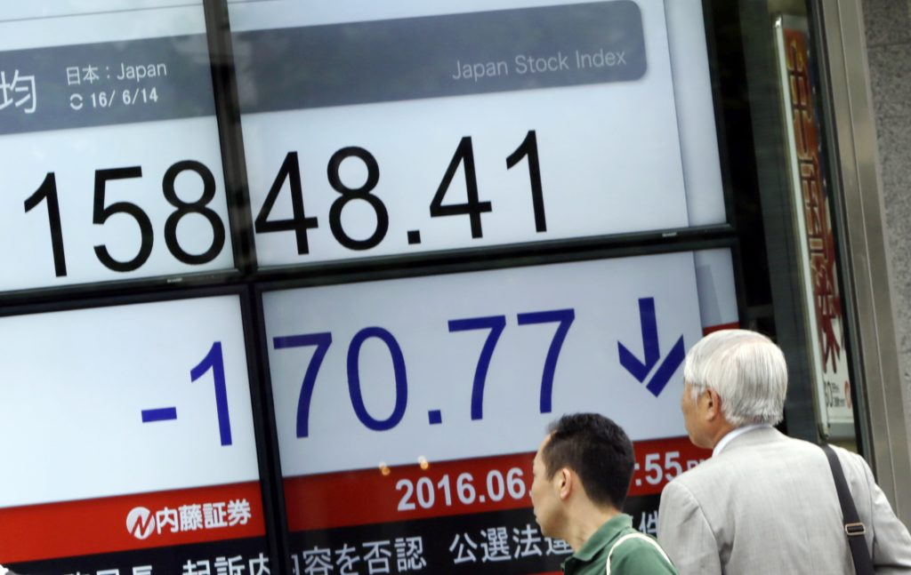 Pedestrians look at an electronic stock board showing Japan's Nikkei 225 index at a securities firm in Tokyo Tuesday, June 14, 2016. Asian stock markets mostly lower Tuesday tracking Wall Street's decline, as jittery investors awaited the U.S. Federal Reserve's decision on interest rates and Britain's vote on European Union membership. (AP Photo/Eugene Hoshiko)