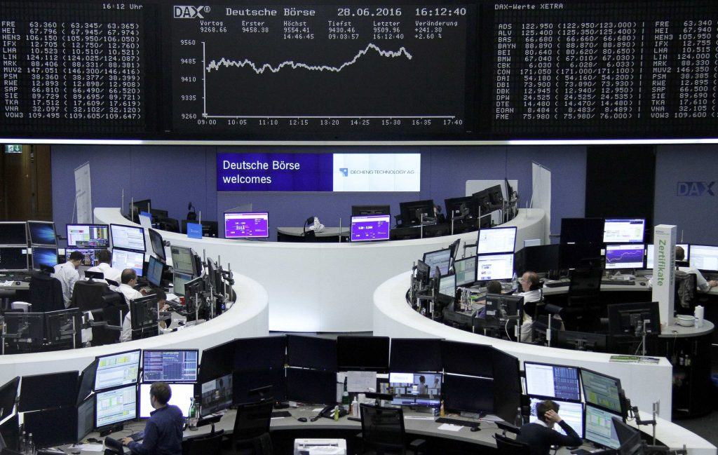 Traders work at their desks in front of the German share price index, DAX board, at the stock exchange in Frankfurt, Germany, June 28, 2016. REUTERS/Staff/Remote