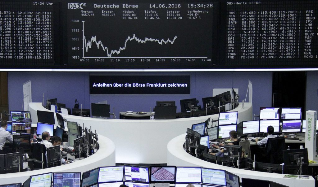 Traders work at their desks in front of the German share price index, DAX board, at the stock exchange in Frankfurt, Germany, June 14, 2016. REUTERS/Staff/Remote