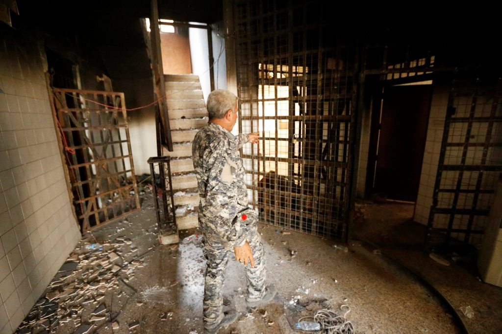 A member of Iraqi government forces walks inside a burnt out prison cell belonging to Islamic State militants in Falluja after government forces recaptured the city from Islamic State militants, Iraq, June 27, 2016. REUTERS/Thaier Al-Sudani