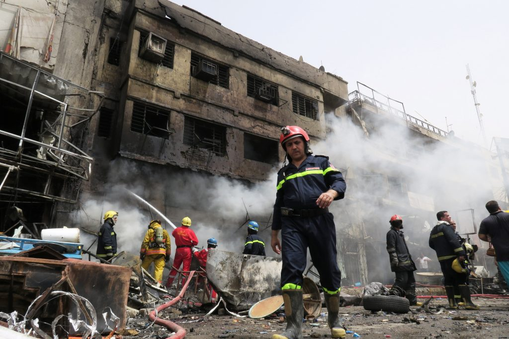 Firemen hose down a burning building at the site of car bomb attack in Baghdad al-Jadeeda, an eastern district of the Iraqi capital, June 9, 2016. REUTERS/Khalid al Mousily