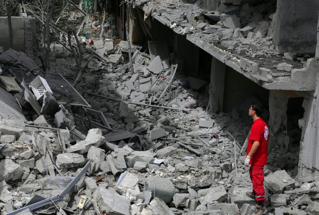 A member of the Syrian Arab Red Crescent inspects a site hit by an airstrike in the rebel-controlled city of Idlib, Syria June 15, 2016. REUTERS/Ammar Abdullah