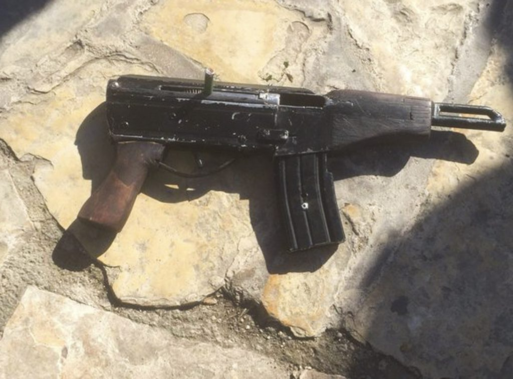 This undated photo provided by the Israeli Police shows a handmade gun produced in Yehudah and Shomron. Welded together from spare gun parts and pipes, the gun looks like a handgun but with an extended barrel and a long magazine of bullets. (Israeli Police via AP)