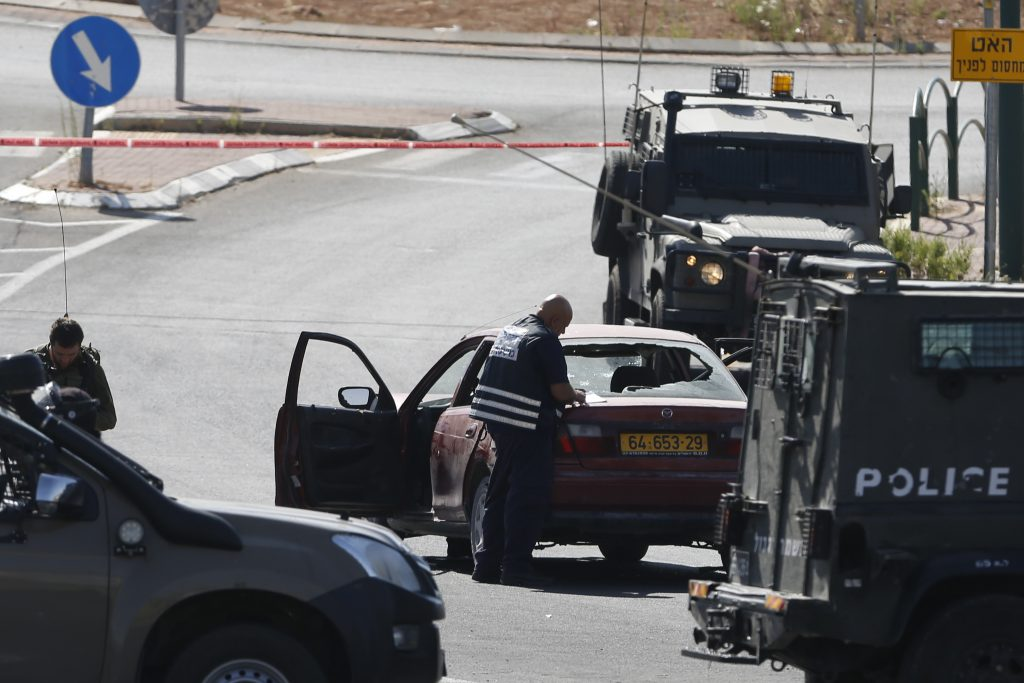 An Israeli policeman takes notes on the car used by a female Palestinian terrorist at the entrance to the  Kiryat Arba on Friday. (AP Photo/Nasser Shiyoukhi)