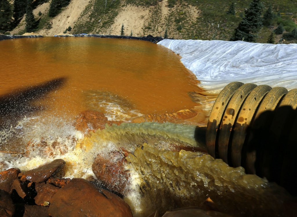 In this Aug. 14, 2015, photo, water flows through a series of sediment retention ponds built to reduce heavy metal and chemical contaminants from the Gold King Mine wastewater accident, in the spillway downstream from the mine, outside Silverton, Colo. (AP Photo/Brennan Linsley, File)