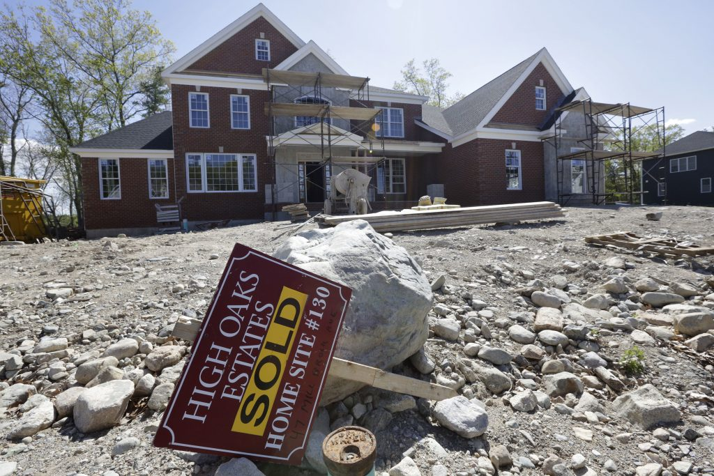 "A ""Sold"" sign rests in front of a house under construction, in Walpole, Mass.  (AP Photo/Steven Senne, File)"
