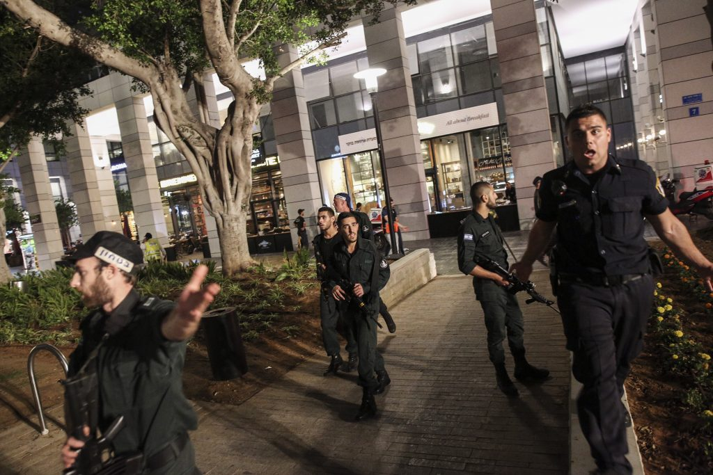 Israeli security forces at the scene where terrorists opened fire and killed three people, wounding others, at the Sarona Market shopping center in Tel Aviv, Wednesday night. (Miriam Alster/Flash90 )