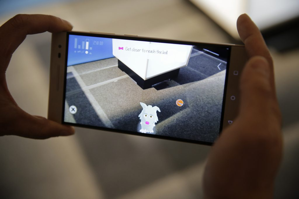 Sam Vang demonstrates playing with a virtual pet on the new Phab2 Pro phone at the Lenovo Tech World event in San Francisco on Thursday. (AP Photo/Eric Risberg)