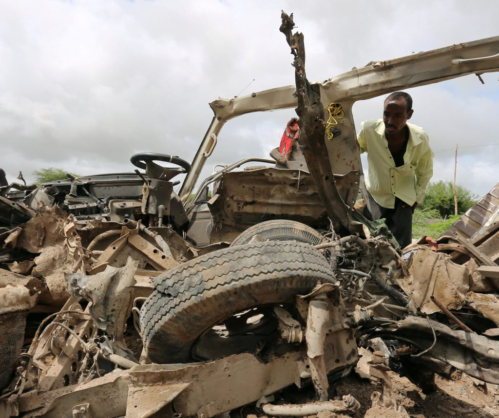 Residents gather to look at the wreckage of a minibus destroyed in roadside bomb in Lafoole village near Somalia's capital Mogadishu, June 30, 2016 REUTERS/Feisal Omar