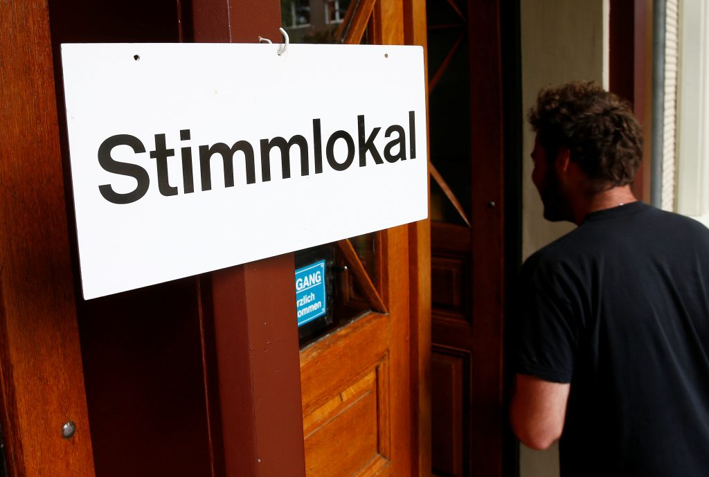 """People arrive in a ballot office to vote on whether to give every adult citizen a basic guaranteed monthly income of 2,500 Swiss francs ($2,560), in a school in Bern, Switzerland, June 5, 2016. The sign reads, """"Ballot office"""". REUTERS/Ruben Sprich"""