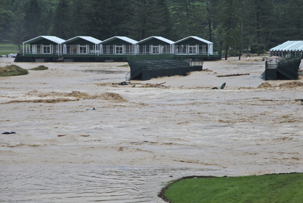 This Thursday June 23, 2016 image provided by the Greenbrier shows flooding on the 17th green of the Old White Course at the Greenbrier in White Sulphur Springs, W. Va. Severe flooding hit the area that is scheduled to host a PGA tour event in two weeks. (Cam Huffman/The Greenbrier via AP)