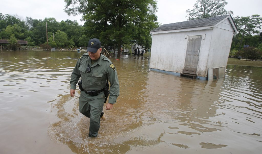 West Virginia State Trooper C.S. Hartman, walks from a shed that he checked out as he and other crews search homes in Rainelle, W. Va., Saturday, June 25, 2016. Heavy rains that pummeled West Virginia left multiple people dead, and authorities said Saturday that an unknown number of people in the hardest-hit county remained unaccounted for. (AP Photo/Steve Helber)
