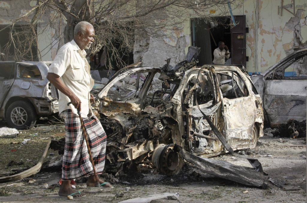 A Somali man walks past a destroyed vehicle at the scene after a bomb attack on Ambassador Hotel in Mogadishu, Somalia, Thursday, June 2, 2016. Somalia's Islamic extremist rebels, al-Shabab, stormed the hotel, often frequented by government officials and business executives, killing people and taking a number of hostages, police said. (AP Photo/Farah Abdi Warsameh)