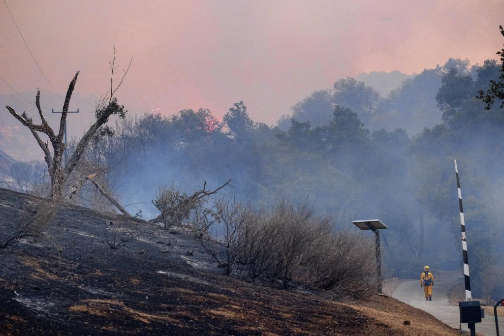 A firefighter walks down a road past a burnt out hillside as fire continues to burn in the foothills outside of Calabasas, Calif. on Saturday, June 4, 2016. A fast-moving brush fire sweeping through hills northwest of downtown Los Angeles has damaged homes and prompted neighborhood evacuations. Los Angeles County fire officials now say the brushfire is threatening about 3,000 homes in the Calabasas neighborhood. (AP Photo/Richard Vogel)