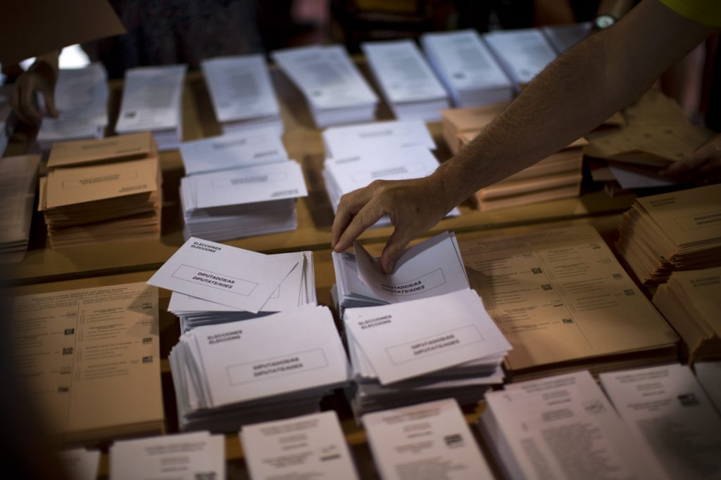 A man picks a ballot paper before casting his vote for the national elections in Barcelona, Spain, Sunday, June. 25, 2016. Spaniards are voting in a general election, just six months after a last unsuccessful attempt to pick a new government. (AP Photo/Emilio Morenatti)