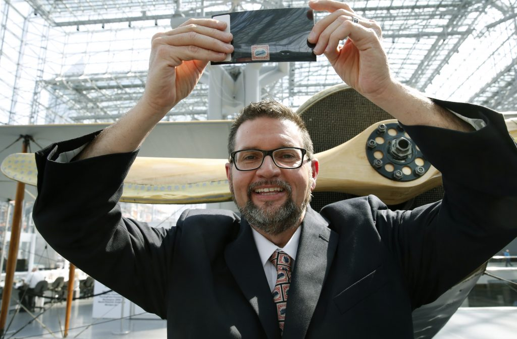 """American Philatelic Society executive director Scott D. English on Thursday holds an """"Inverted Jenny,"""" a 1918 stamp stolen in 1955, that was returned to its rightful owner at the Jacob Javits Center in New York. (AP Photo/Kathy Willens)"""