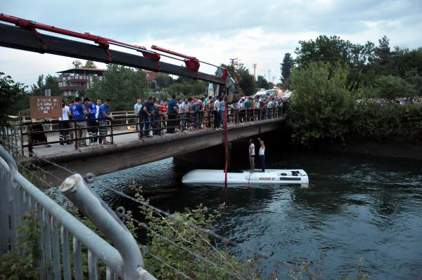 Turkish rescuers lift a bus from a canal near Osmaniye, Turkey, Monday, June 6, 2016. The bus carrying school children, teachers and parents plunged into an irrigation canal in southern Turkey, killing at least 14 people, six of them children, officials and reports said Monday. Several other people were injured in the accident which occurred late Sunday as the bus was returning from a school trip to a national park and museum in the southern province of Osmaniye, Gov. Kerem Al said.(DHA via AP) TURKEY OUT