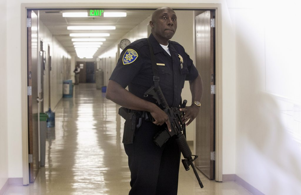 A University of California Police Officer is seen behind a glass door, as he secures the entrance to the Engineering IV annex at UCLA campus near the scene of a fatal shooting at the University of California, Los Angeles, Wednesday, June 1, 2016, in Los Angeles. Los Angeles police chief says shooting at UCLA was murder-suicide. (AP Photo/Damian Dovarganes)