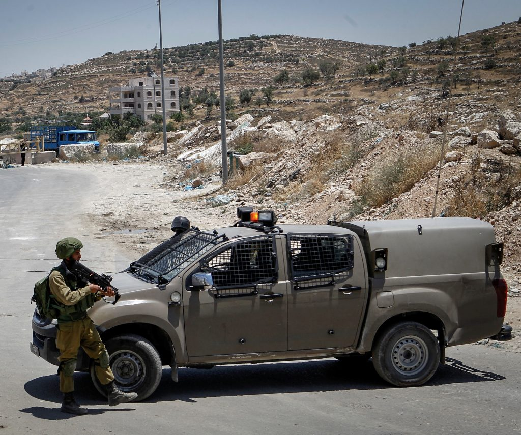 Israeli soldiers hold a temporary checkpoint at the entrance to the Palestinian village of Yatta, home of the two terrorists who carried out the shootings in Tel Aviv. (Wisam Hashlamoun/Flash90)