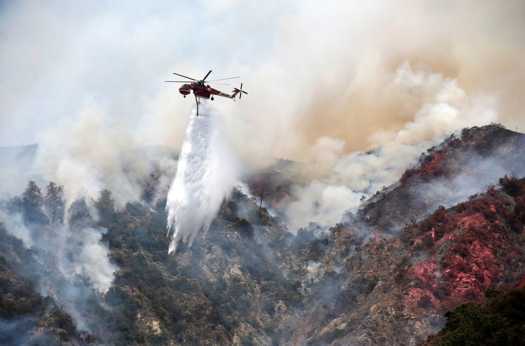A helicopter drops water on a wildfire in the San Gabriel mountains as it attacks the flames near Duarte, California, U.S. June 21, 2016. REUTERS/Lucy Nicholson