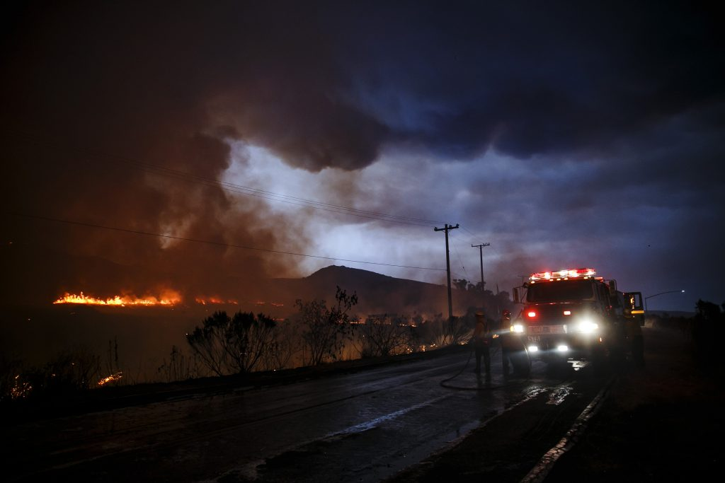 Firefighters make a defensive move on the front lines of the Sherpa Fire to avoid it from moving onto the 101 freeway, along Calle Real Road, in Goleta, Calif., on Thursday. (Marcus Yam/Los Angeles Times/TNS)