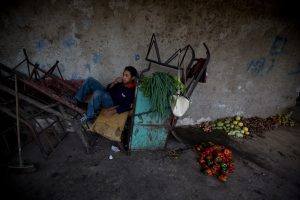 Antonio Gutierrez, who works driving a cart rests next to vegetables and fruits he and a friend collected from the trash of the Coche public market in Caracas, Venezuela. (AP Photo/Fernando Llano)