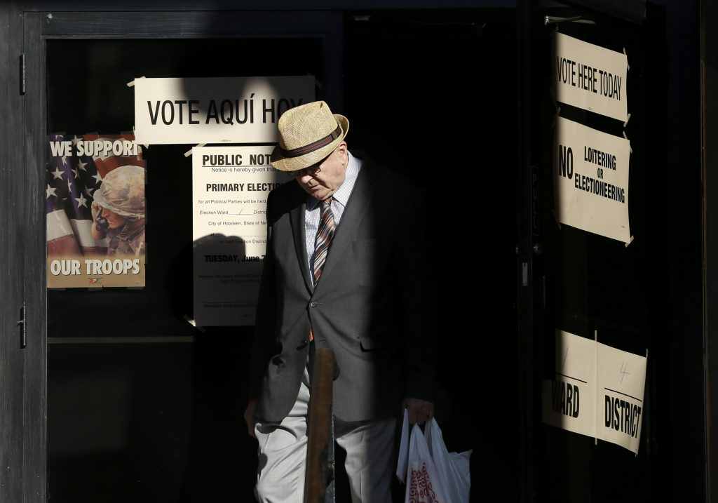 A man leaves a polling site Tuesday after voting in Hoboken, N.J. (AP Photo/Seth Wenig)