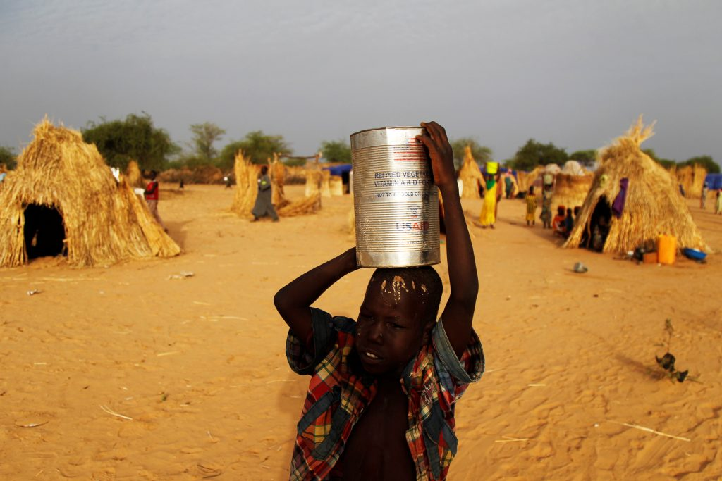 A boy carries water in a can that once held food aid at the Boudouri site for displaced persons outside the town of Diffa in southeastern Niger June 17, 2016. REUTERS/Luc Gnago