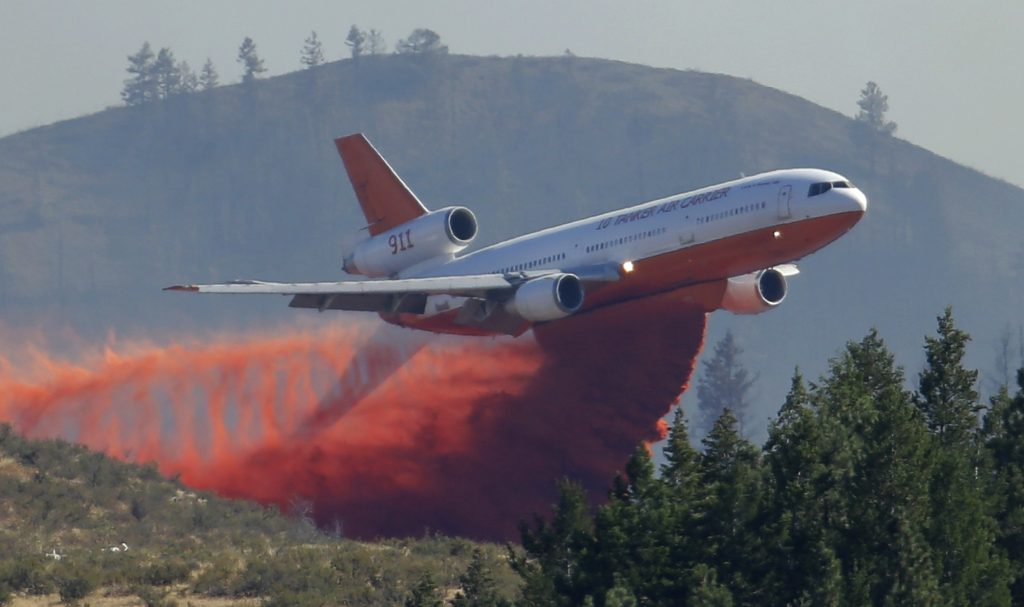 A tanker airplane drops fire retardant on a wildfire. (AP Photo/Ted S. Warren, File)