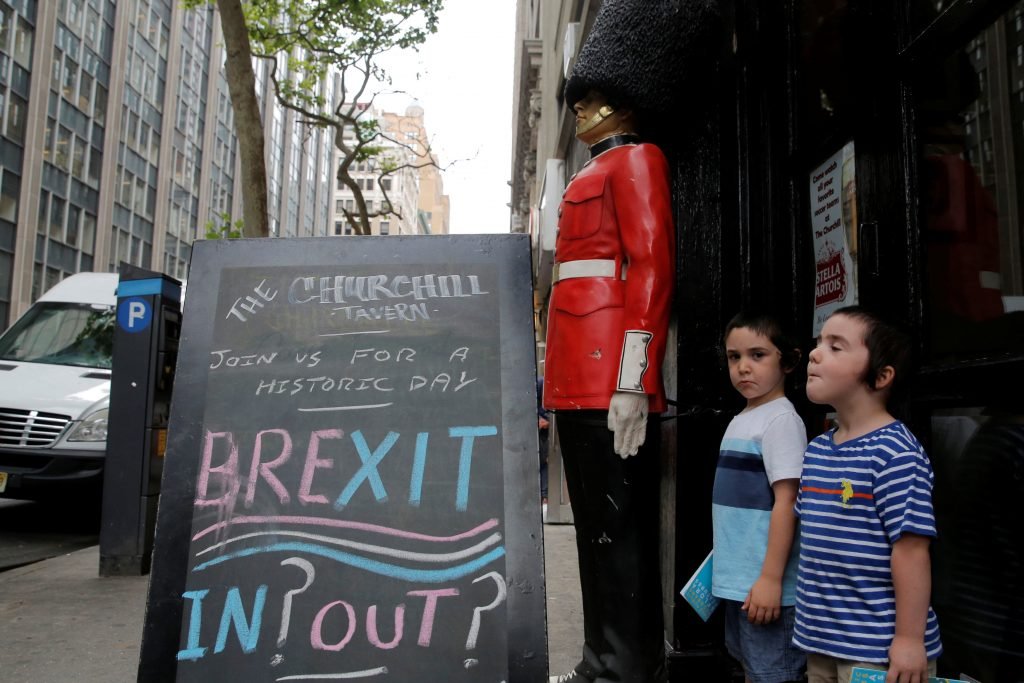 """Children pose next to a chalkboard advertising a Brexit viewing event at """"The Churchill Tavern"""", a British theme bar, on the day where Britain votes whether or not to remain in the European Union in the Manhattan borough of New York, U.S., June 23, 2016. REUTERS/Andrew Kelly"""