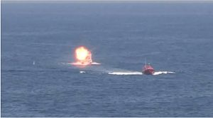 A small boat approaching the USS Ponce explodes during testing of the Office of Naval Research-funded Laser Weapons System (LaWS) while in the Persian Gulf. (U.S. Navy video screen grab)
