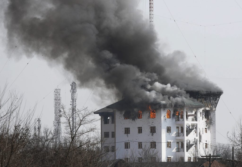 In this Feb. 22, 2016, photo, smoke rises from a building where suspected militants have taken refuge during a gun battle in Pampore, Kashmir. (AP Photo/Mukhtar Khan, File)