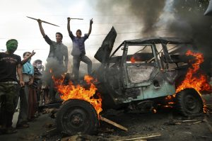 In this Aug. 4, 2010, photo, Kashmiri protesters shout slogans near a burning government vehicle after they set it on fire during a protest over Indian rule over the Himalayan region at Barthana neighborhood in Srinagar, India. (AP Photo/Dar Yasin, File)