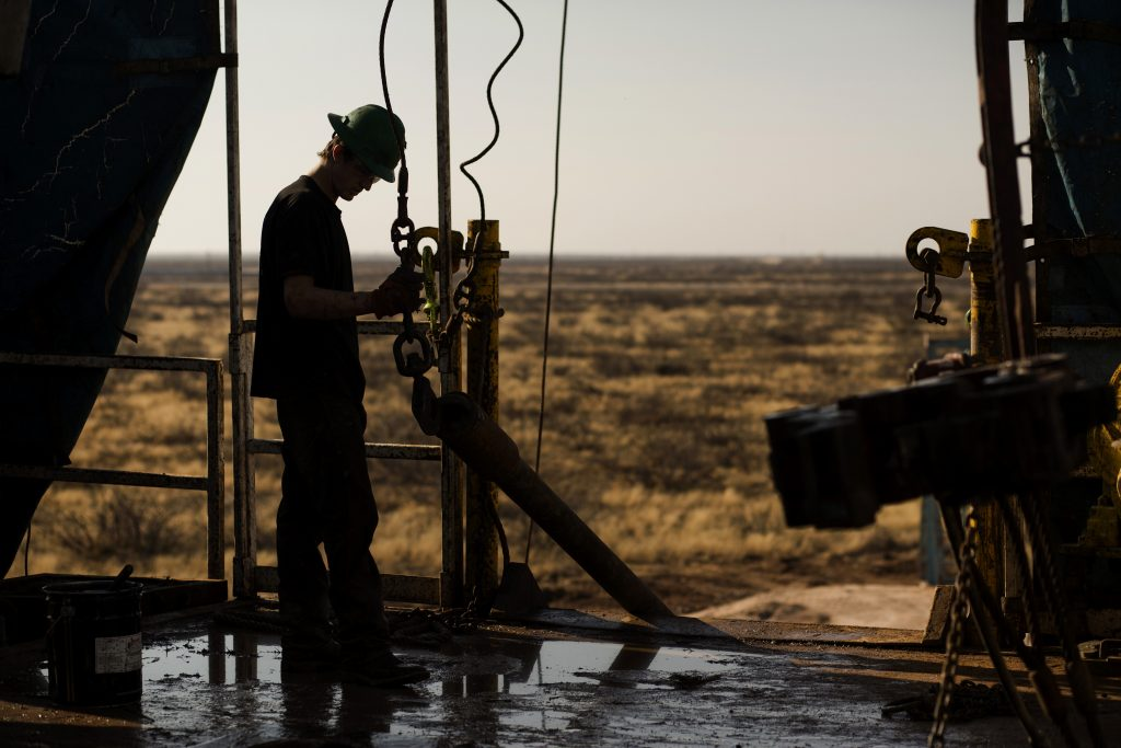 A worker waits to connect a drill bit, in the Permian basin outside of Midland, Texas. (Bloomberg photo by Brittany Sowacke)