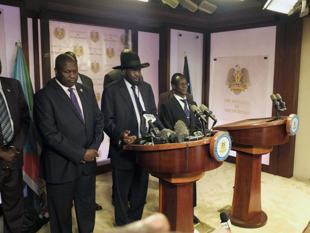 South Sudanese President Salva Kiir (C), flanked by former rebel leader Riek Machar (L) and other government officials, addresses a news conference at the Presidential State House in Juba, South Sudan, on Friday. (Reuters/Stringer)
