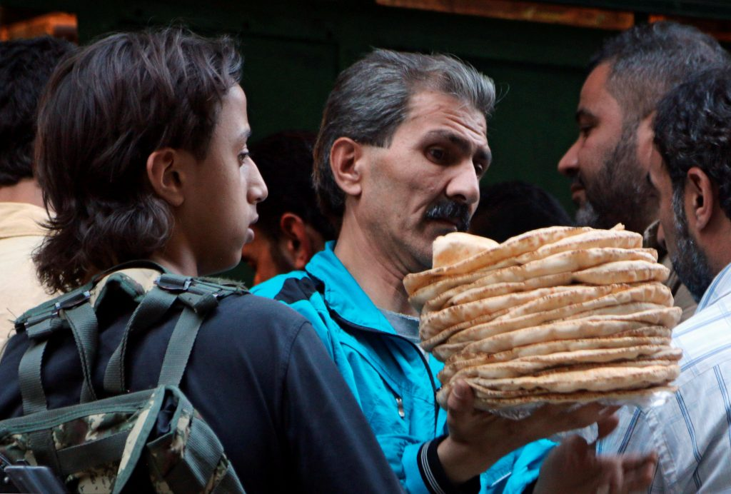 A man holds bread as a rebel fighter stands guard in the rebel held al-Shaar neighborhood of Aleppo, Syria July 14, 2016. REUTERS/Abdalrhman Ismail